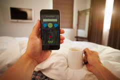 Man In Bed Looking At Health Monitoring App On Mobile Phone Royalty Free Stock Image