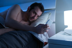 Man in bed with mobile phone Royalty Free Stock Photography