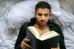 Man in bed with open shirt and pecs reading hardback book. Handsome, man in bed with open black shirt and pecs reading hardback book royalty free stock photography