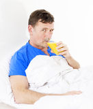 Man in bed with orange juice Stock Images