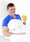 Man in bed with orange juice Stock Photography