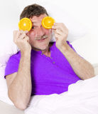 Man in bed with oranges Stock Photo