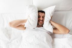 Man in bed with pillow suffering from noise. People, bedtime and rest concept - man lying in bed with pillow suffering from noise at home royalty free stock photo