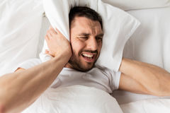 Man in bed with pillow suffering from noise. People, bedtime and rest concept - man lying in bed with pillow suffering from noise at home stock photography