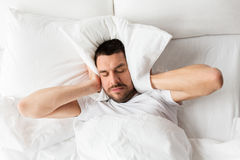 Man in bed with pillow suffering from noise. People, bedtime and rest concept - man lying in bed with pillow suffering from noise at home royalty free stock images