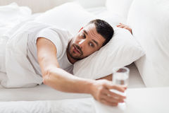 Man in bed and reaching to glass of water at home Stock Photos