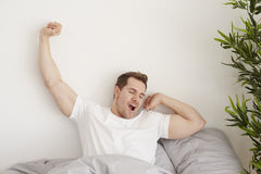 Man at the bed. Rise and shine in the morning Stock Photography