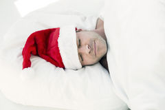 Man in bed with santa hat Royalty Free Stock Photos