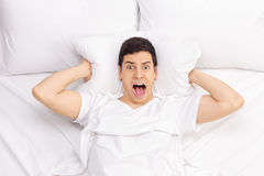 Man in bed screaming Stock Image