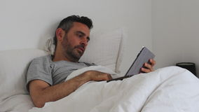 Man in bed with smartphone and tablet stock video footage