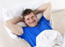Man in bed smiling Stock Photo