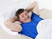 Man in bed smiling Stock Image