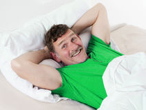 Man in bed smiling Stock Images