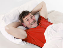 Man in bed smiling. Man in his fifties lying in bed and smiling Royalty Free Stock Photos