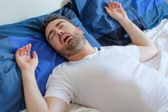 Man in bed suffering for sleep apnea syndrome Stock Image
