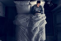 Man on bed using his tablet royalty free stock image