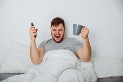 Man in bed watch interesting match. Sport fan in bed watch interesting sport match Stock Photos