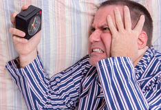 Man in bed watching alarm clock Stock Photo