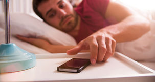 Man In Bed Woken By Alarm On Mobile Phone royalty free stock image