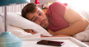 Man In Bed Woken By Alarm On Mobile Phone Royalty Free Stock Images