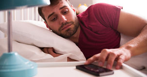 Man In Bed Woken By Alarm On Mobile Phone Stock Images