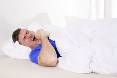 Man in bed yawning Royalty Free Stock Photo