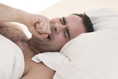 Man in bed yawning Stock Photo