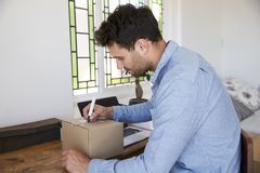 Man In Bedroom Running Business From Home Labeling Goods Stock Photography