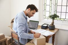 Man In Bedroom Running Business From Home Labeling Goods Royalty Free Stock Photos