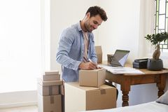 Man In Bedroom Running Business From Home Labeling Goods Stock Images