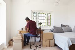 Man In Bedroom Running Business From Home Labeling Goods Royalty Free Stock Photography