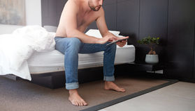 Man in bedroom using touch screen computer Stock Image