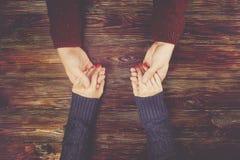 Man beeld van de de handen het hoogste mening van de holdingsvrouw ` s op donkere houten achtergrond Paar in liefdeconcept Royalty-vrije Stock Afbeeldingen