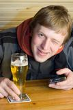 Man with beer. Man with beaker of beer and palm-size computer. Winking and smiling Stock Photo