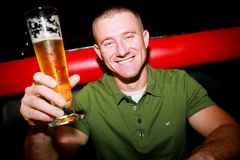Man with Beer. A sexy man smiling holding a beer Royalty Free Stock Photos