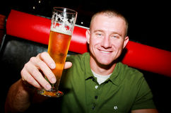 Man with Beer. A sexy man smiling holding a beer Stock Photography