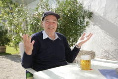 Man with Beer. 75 year old man sitting in garden of inn enjoying his first beer after recovering from surgery to implant heart pacemaker stock images