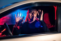 Man with beer bottle in car surrendering to police. Young caucasian man with beer bottle in car surrendering to police. Driving under alcohol influence Stock Photos