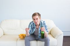Man with beer and chips watching TV at home stock images