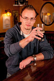 Man with a beer giving a toast. Man with a beer in bar giving a toast and smiling Royalty Free Stock Photos