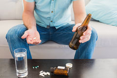 Man with a beer and his medicine laid Stock Photos