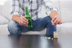 Man with a beer and his medicine laid Stock Images