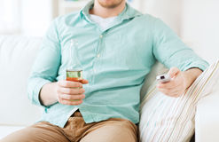 Man with beer and remote control at home Stock Photography