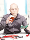 Man with beer think about repairing Stock Image