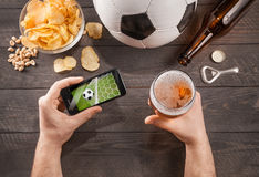 Man with beer watching soccer game on smarphone royalty free stock photography