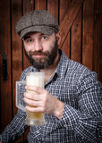 Man with beer. A man wearing a cap with a beer mug Stock Image