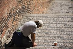 Man beggar kneeling begging money from people. Man beggar kneeling begging money from Czechia people and foreigner travelers at walkway for go to visit and Royalty Free Stock Photography