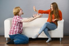 Man begging for forgiveness his woman. Man begging women who is sitting on sofa for forgiveness. Couple after fight or argue. Female showing speak to hand stock photo