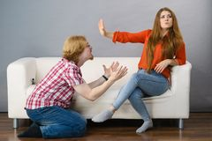 Man begging for forgiveness his woman. Man begging women who is sitting on sofa for forgiveness. Couple after fight or argue. Female showing speak to hand royalty free stock images