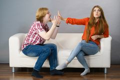 Man begging for forgiveness his woman. Man begging women who is sitting on sofa for forgiveness. Couple after fight or argue. Female showing speak to hand stock photos